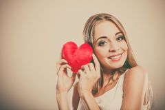 Smiling woman holding red heart love symbol. Valentines day love and relationships concept. Blonde long hair young woman holding red heart love symbol studio stock image