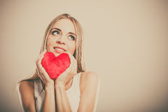 Smiling woman holding red heart love symbol. Valentines day love and relationships concept. Blonde long hair young woman holding red heart love symbol studio royalty free stock photo