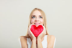 Smiling woman holding red heart love symbol. Valentines day love and relationships concept. Blonde long hair young woman holding red heart love symbol studio stock photo