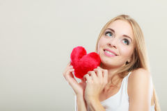 Smiling woman holding red heart love symbol. Valentines day love and relationships concept. Blonde long hair young woman holding red heart love symbol studio stock photos