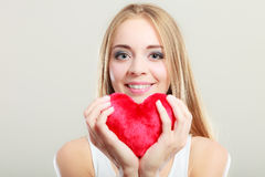 Smiling woman holding red heart love symbol Royalty Free Stock Photography
