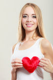 Smiling woman holding red heart love symbol. Valentines day love relationships or health care concept. Blonde young woman holding red heart love symbol on her stock images