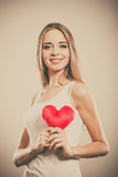 Smiling woman holding red heart love symbol. Valentines day love relationships or health care concept. Blonde young woman holding red heart love symbol on her royalty free stock photo