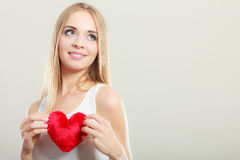 Smiling woman holding red heart love symbol Stock Photography