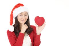 Young woman in Santa Claus cap. Smiling woman holding red heart love symbol royalty free stock photography