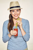 Smiling woman holding red juce glass with straw wearing modern h Royalty Free Stock Photos
