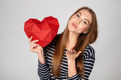 Smiling woman holding red polygonal paper heart shape Royalty Free Stock Images