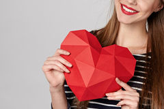 Smiling woman holding red polygonal paper heart shape Stock Photography
