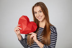 Smiling woman holding red polygonal paper heart shape Royalty Free Stock Photography