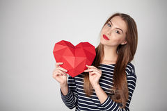 Smiling woman holding red polygonal paper heart shape Stock Image