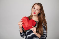 Smiling woman holding red polygonal paper heart shape Royalty Free Stock Photos