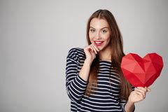 Smiling woman holding red polygonal paper heart shape Stock Photo