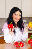 Smiling woman holding red and yellow peppers Stock Photography
