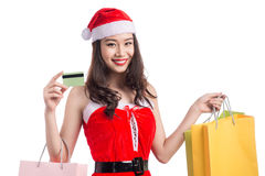 Smiling woman holding shopping bags before christmas showing cre Stock Photo