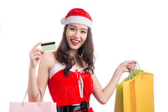 Smiling woman holding shopping bags before christmas showing cre. Dit card. Focus on card Stock Photos