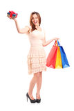 Smiling woman holding a shopping bags and a gift Stock Photography