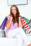 Smiling woman holding shopping bags in hands. Smiling pretty woman sitting on sofa at home and holding shopping bags in hands Royalty Free Stock Image