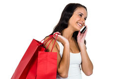 Smiling woman holding shopping bagsand using smartphone Stock Photos