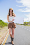 Smiling woman holding sign while hitchhiking. On a deserted road in summertime Stock Image