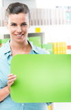 Smiling woman holding sign at supermarket Stock Photos