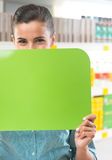 Smiling woman holding sign at supermarket Royalty Free Stock Photography