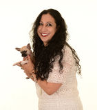 Smiling woman holding small dog. Attractive smiling woman with long dark hair wearing white lace dress holding tiny cream, brown and black puppy dog, white Stock Images