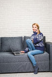 Smiling woman holding a smartphone and calling while using laptop on sofa Stock Images