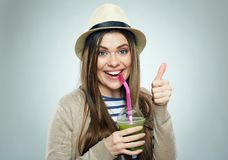 Smiling woman holding smoothie drink shows thumb up. Stock Photo