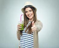Smiling woman holding smoothie drink shows thumb up. Stock Photography