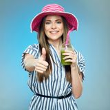 Smiling woman holding smoothie drink shows thumb up. Royalty Free Stock Photos