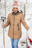Smiling woman holding snow shovel Stock Image