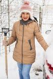 Smiling woman holding snow shovel Stock Image