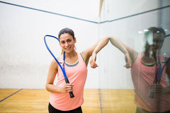 Smiling woman holding a squash racket. In the squash court Royalty Free Stock Photography