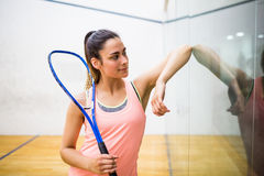 Smiling woman holding a squash racket. In the squash court Royalty Free Stock Photo