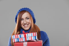 Smiling Woman Holding Stack of Christmas Presents. Smiling Woman with Red Hair Holding Stack of Wrapped Christmas Presents in Studio royalty free stock photo