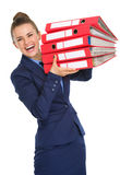 Smiling woman holding stack of files up in the air and laughing Royalty Free Stock Image