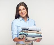 Smiling woman holding stack of warm winter clothes. Portrait isolated on white Stock Photos