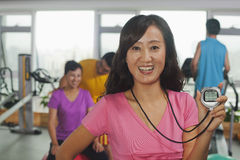 Smiling woman holding stopwatch in foreground, people working out in the gym in the background Royalty Free Stock Images