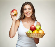Smiling woman holding straw basket with fruits. Studio isolated Stock Images