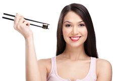 Smiling woman holding sushi roll with a chopsticks Royalty Free Stock Photo