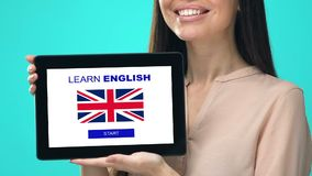 Smiling woman holding tablet with learn English language test, educational app. Stock footage stock footage