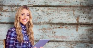 Smiling woman holding tablet PC against wall Stock Photo