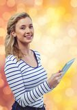 Smiling woman holding tablet PC over blur background Stock Image