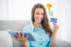 Smiling woman holding tablet and showing her credit card Royalty Free Stock Photo