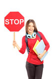 Smiling woman holding a traffic sign stop and notebooks Stock Image
