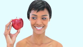 Smiling woman holding two apples. Against a white background stock video