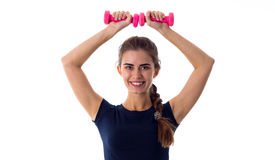 Smiling woman holding two dumbbells over her head Royalty Free Stock Photo