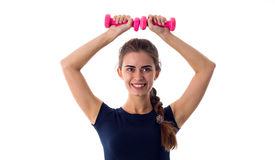 Smiling woman holding two dumbbells over her head Stock Photos