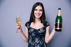 Smiling woman holding two glass and bottle of champagne Royalty Free Stock Photography