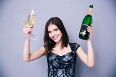 Smiling woman holding two glass and bottle of champagne Royalty Free Stock Photos